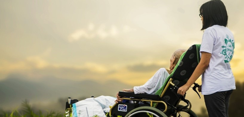 hospice and elderly care jobs: woman providing care to an elder woman in wheelchair